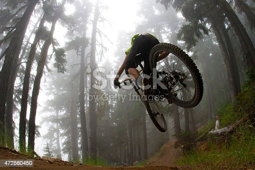 A male mountain bike rider hits a jump on a trail in a forest on a foggy day.
