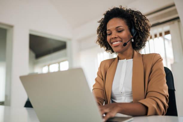 Retrato de ángulo bajo de una mujer feliz usando auriculares usando computadora portátil. - foto de stock