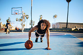 Image of a young woman doing one hand push ups after playing basketball on the courts near Venice beach in Los Angeles, California.