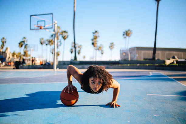 Low angle portrait of a young women doing one hand push ups stock photo