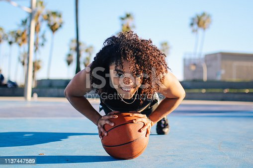 Image of a young woman doing push ups after playing basketball on the courts near Venice beach in Los Angeles, California.