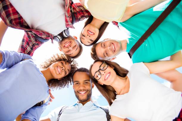 niedrigen winkel porträt von sechs internationalen studenten mit strahlend lächelt, posiert für schuss außerhalb der schule, die aufbauend auf einem himmelshintergrund. versammelten, fröhliche, intelligente und erfolgreiche jugend - high school bilder stock-fotos und bilder
