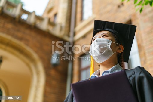 A low angle portrait of a student in graduate gown with a diploma.