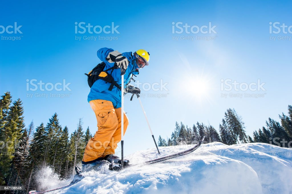 Low angle shot of a skier riding down the slope at ski resort...