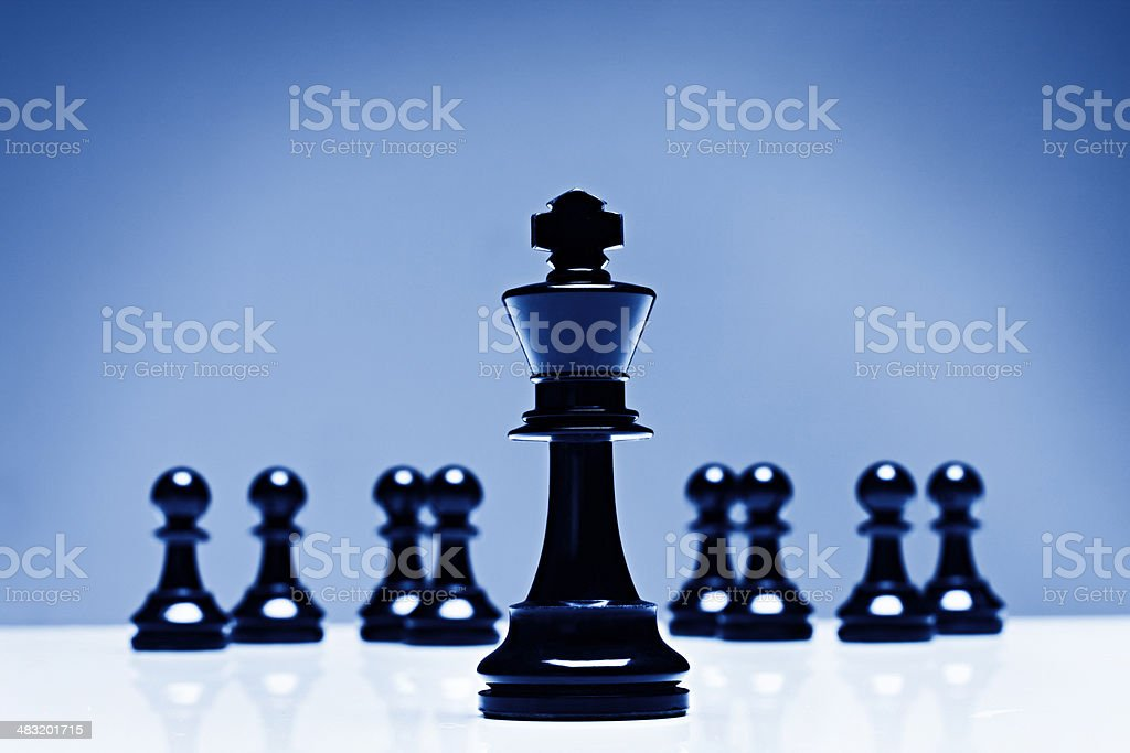 Low angle shot of chess king with pawns in background stock photo