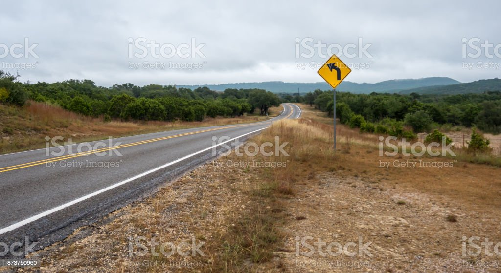Low Angle Shot of Country Road With Yellow TRaffic Sign in the Foreground stock photo