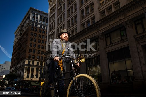 Dramatic portrait of a bearded caucasian man in his late 30s riding his bicycle down a city street. Taken with strobes.
