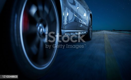 Low angle side view of car driving fast at night .