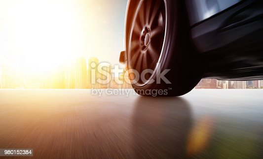 688980174istockphoto Low angle side view of car driving fast 980152384