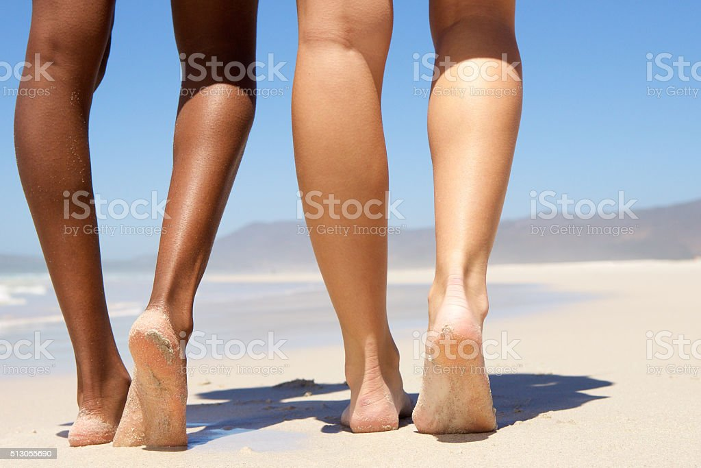 Low angle two women walking barefoot stock photo