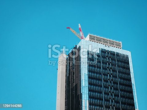 istock Low Angle Vie of Under Construction Building with Cranes on the Roof Floor 1294144265