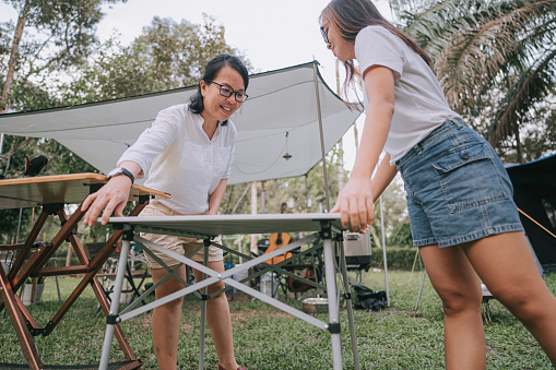 asian chinese mother and daughter setting up picnic table for food preparation at camping site
