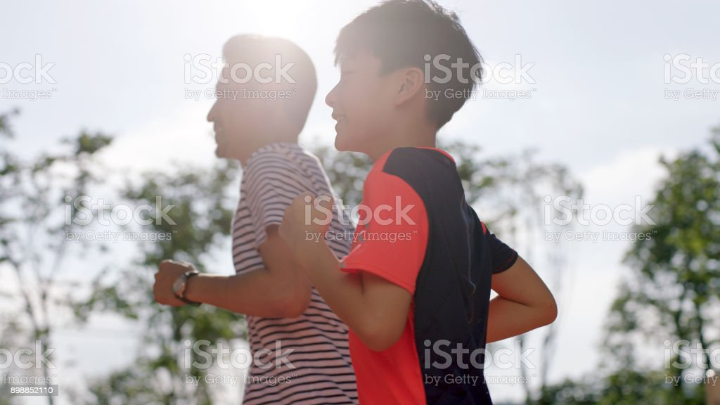 low angle view fo Chinese man & son jogging outdoors in garden back lighted stock photo