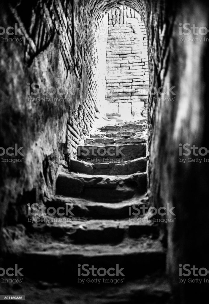 Low angle view looking up stone stairs toward doorway on a path leading to light stock photo