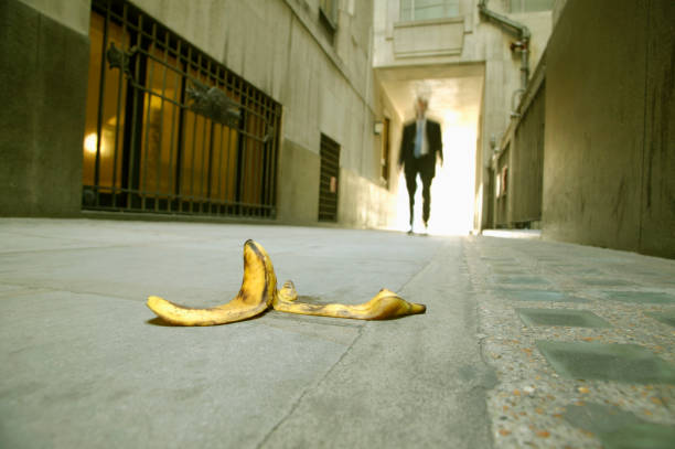 Low angle view of a businessman walking towards a banana skin Low angle view of a businessman walking towards a banana skin themes of careless problems risk safety banana peel stock pictures, royalty-free photos & images