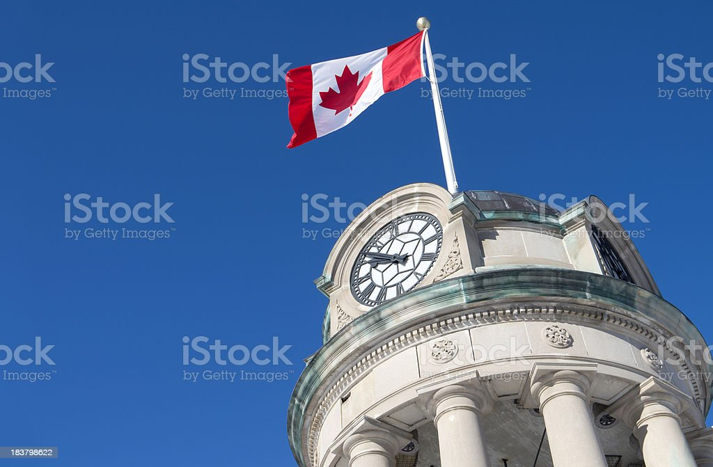 Low angle view of a Canadian flag flying on a clock tower stock photo