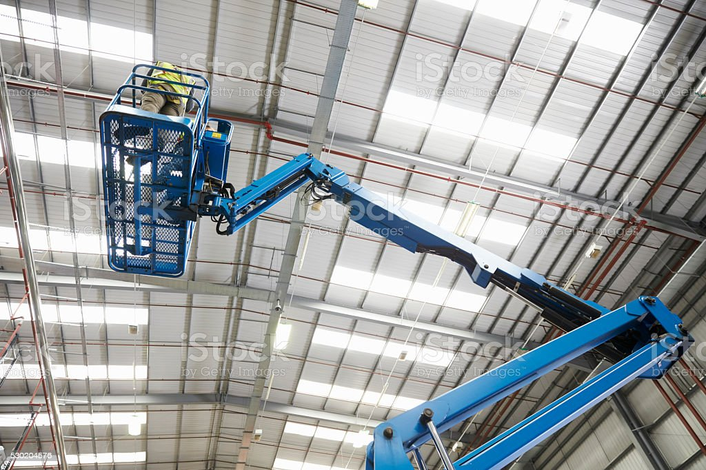 Low angle view of a cherry picker being used in a stock photo