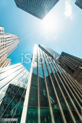 490774222istockphoto Low Angle View of a Contemporary Glass Skyscrapers Reflecting Bright Blue  Sky 1162673083