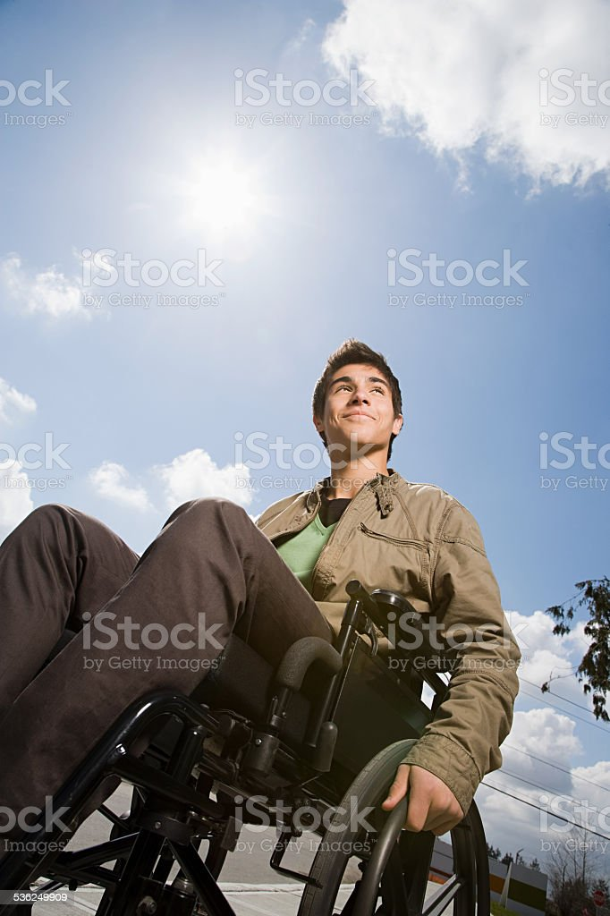 Low angle view of a disabled teenage boy stock photo