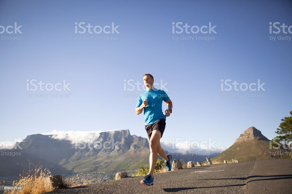 Low angle view of a fit male running along a road stock photo