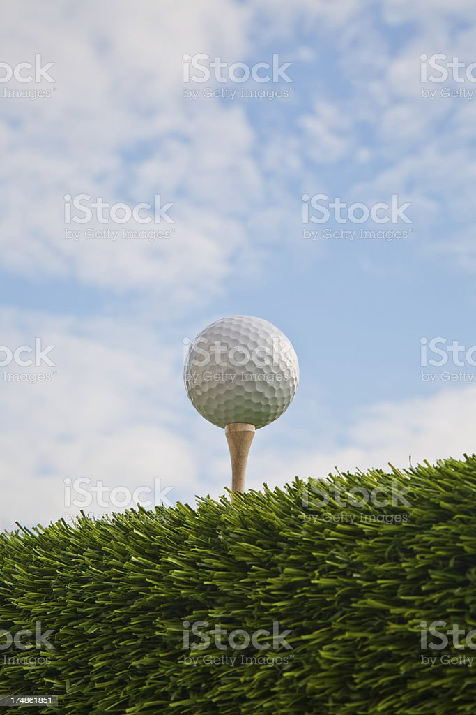 Golf ball on the tee in the grass against soft clouds and blue sky...