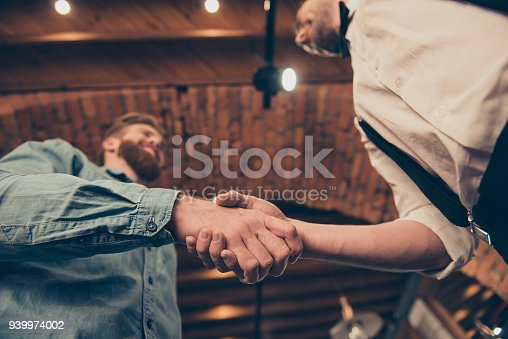 istock Low angle view of a hanshake of the red bearded client and classy dressed stylist of a barber shop in a loft style 939974002