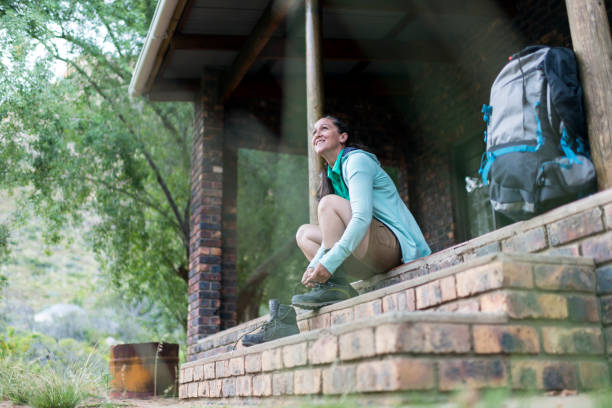 Low angle view of a smiling woman putting her hiking boots on at her cabin stock photo