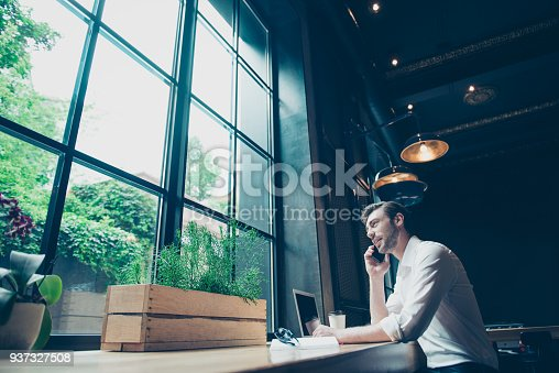 937328186 istock photo Low angle view of a successful young man, having a business conversation,  at work station in a modern coworking, well dressed, smiling, looking in the window 937327508