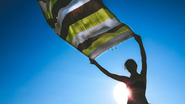 Low angle view of a woman holding a loincloth fabric up in the air to let it dry in the wind stock photo