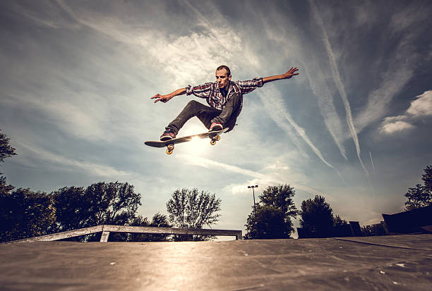 low angle view of a young man skateboarding outdoors. - skateboard stock pictures, royalty-free photos & images