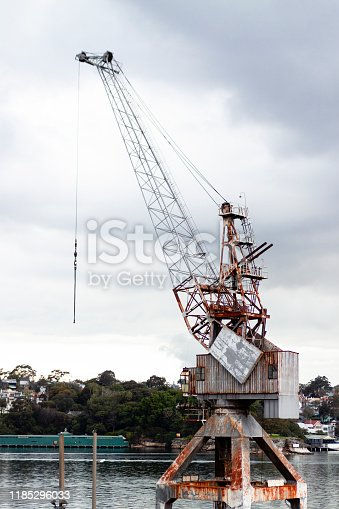 Low angle view of abandoned old rusty crane, background with copy space, vertical composition