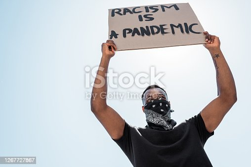 low angle view of african american man with scarf on face holding placard with racism is a pandemic lettering against blue sky