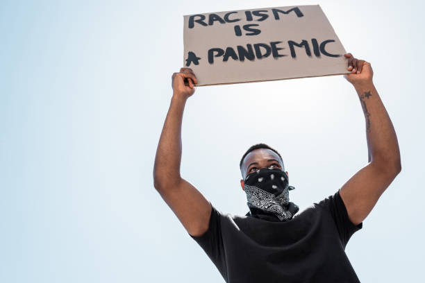 low angle view of african american man with scarf on face holding placard with racism is a pandemic lettering against blue sky stock photo