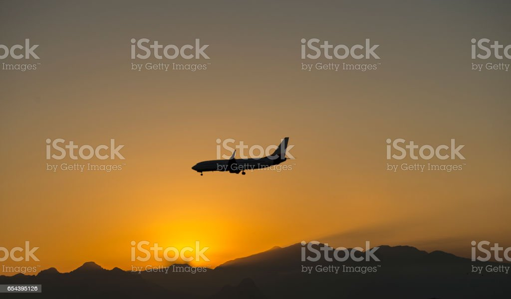 Low angle view of airplane moving at sunset stock photo