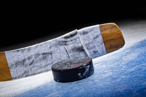 """low angle view of an ice hockey stick with puck sitting on the """"blue line"""" in the spot light - hockey stick stock pictures, royalty-free photos & images"""