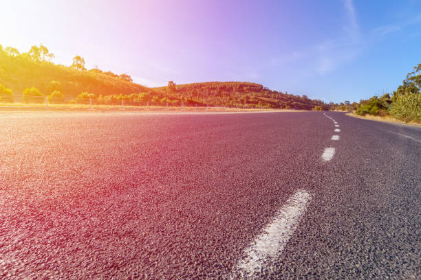 low angle view of asphalt highway with dotted white line at sunset - dotted line stock photos and pictures
