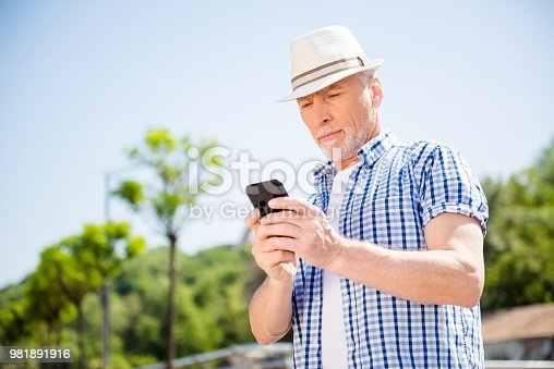 istock Low angle view of attractive business man over blurred street background holding smart phone in hands using 4G internet chatting with friends searching contact. Electronic wireless device concept 981891916