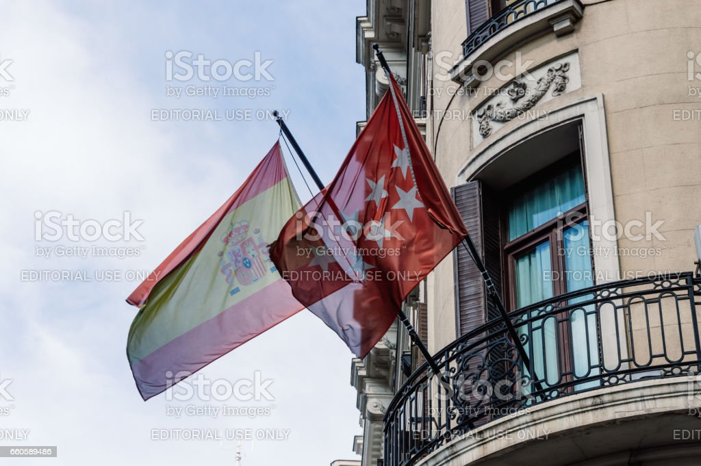 Low angle view of  balcony with spanish and Madrid flags at Gran Via Street in Madrid. stock photo
