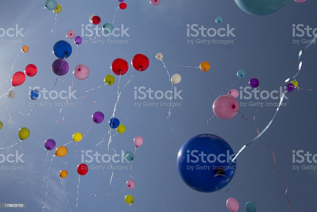 Low angle view of balloons flying into the sky stock photo