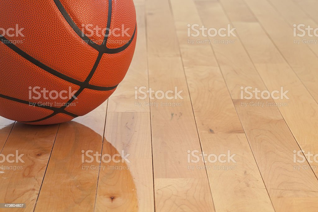 Low angle view of basketball on wooden gym floor stock photo