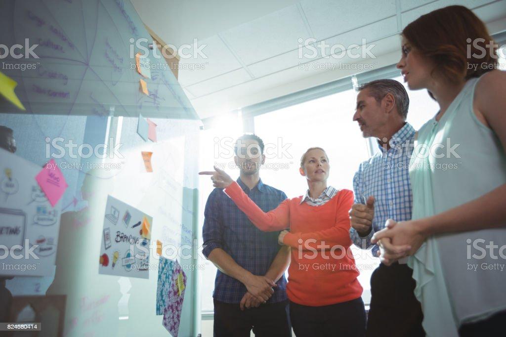 Vue faible angle de collègues de travail, discuter au tableau blanc au bureau - Photo