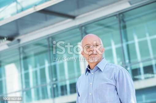 Low angle view of Business man looking off in the distance against backdrop of windows.