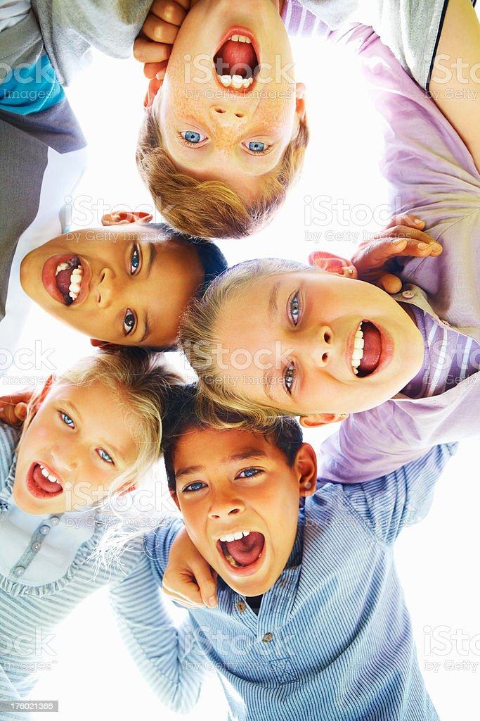 Low angle view of cheerful children huddling together with arm around