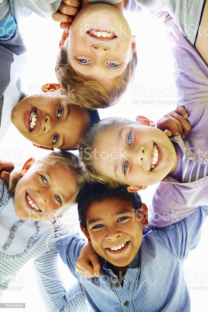 Low angle view of cheerful children huddling together stock photo