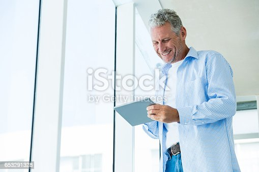 istock Low angle view of cheerful mature man holding tablet 653291328