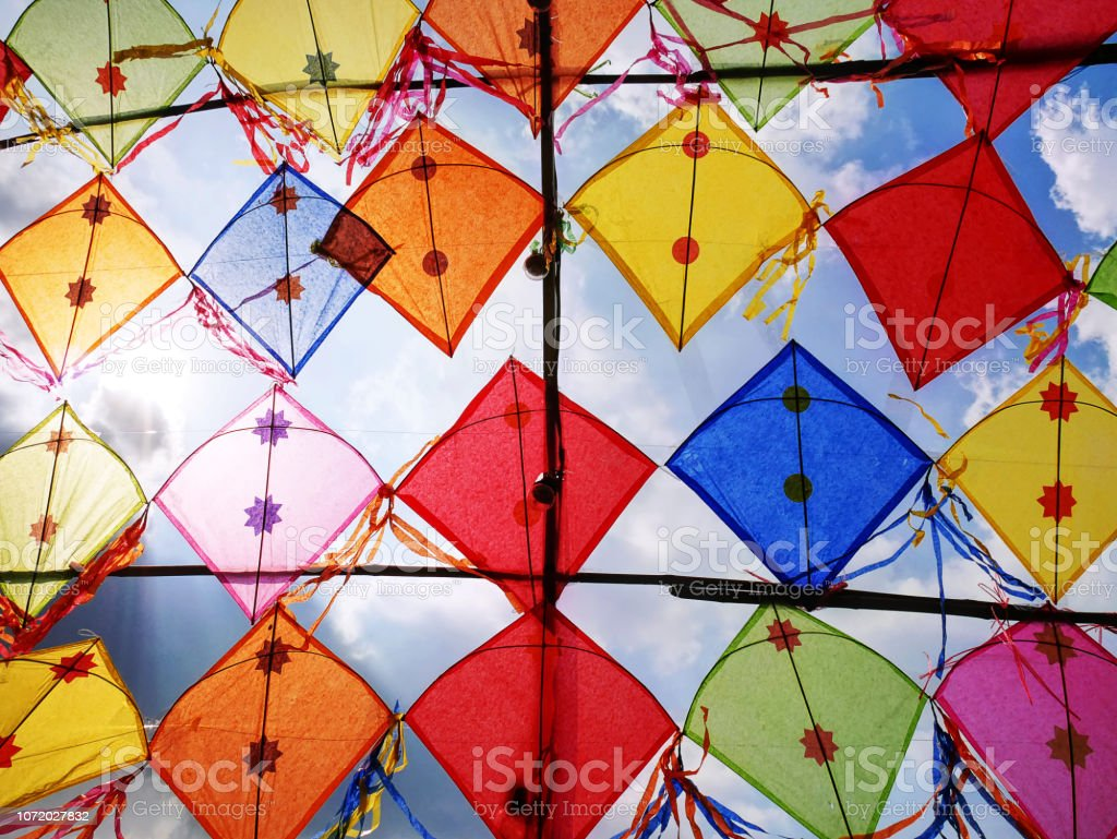 Low Angle View of Colorful Decorative Kites Against Cloudy Sky royalty-free stock photo