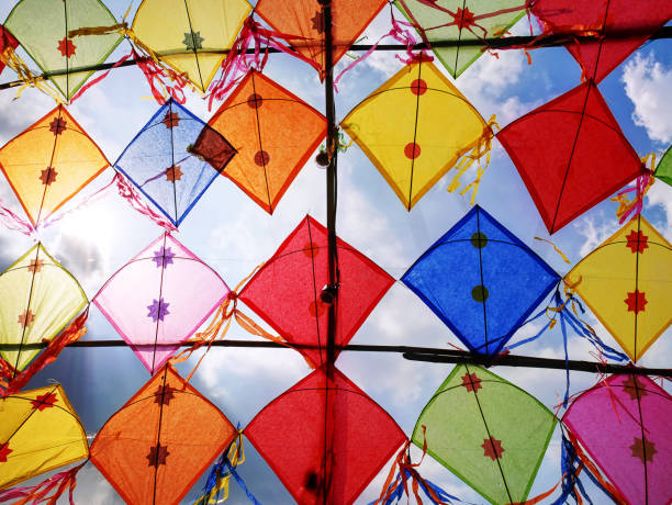 Low Angle View of Colorful Decorative Kites Against Cloudy Sky stock photo