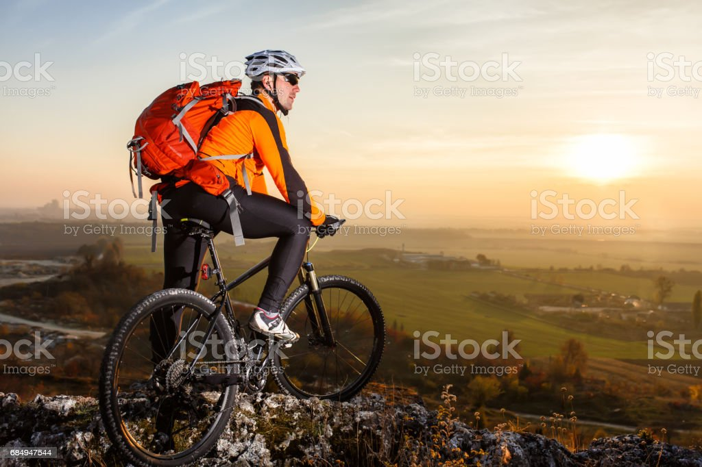 low angle view of cyclist standing with mountain bike on trail at sunset Lizenzfreies stock-foto