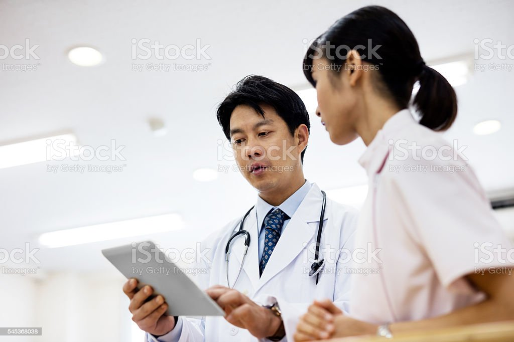 Low angle view of doctor showing digital tablet in hospital stock photo