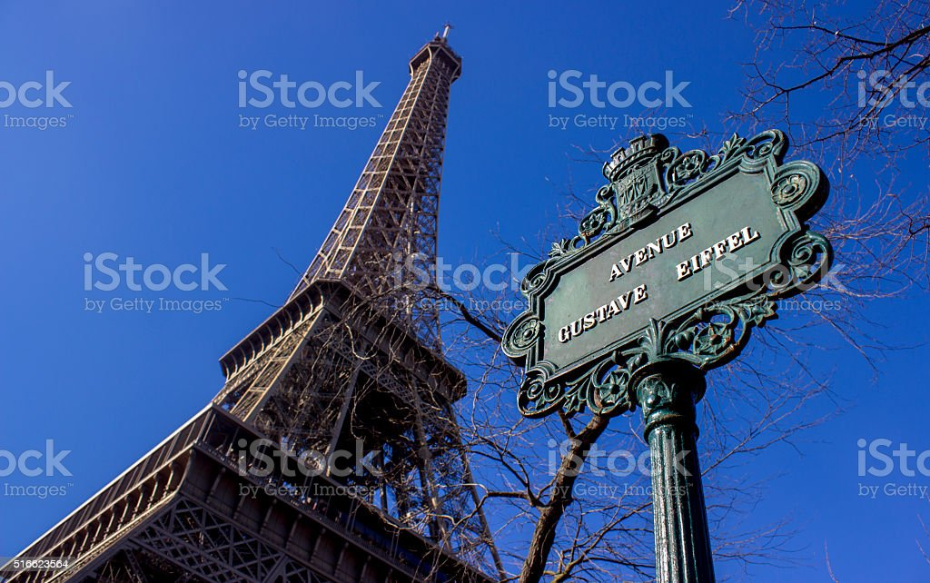 Low angle view of Eiffel tower with Gustave Eiffel sign stock photo